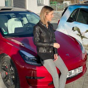 Frau sitzt auf einem roten Auto