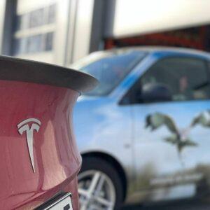 Ein rotes Auto auf der linken Seite und dahinter ist ein Smart mit einem Adler als Beklebung zu sehen