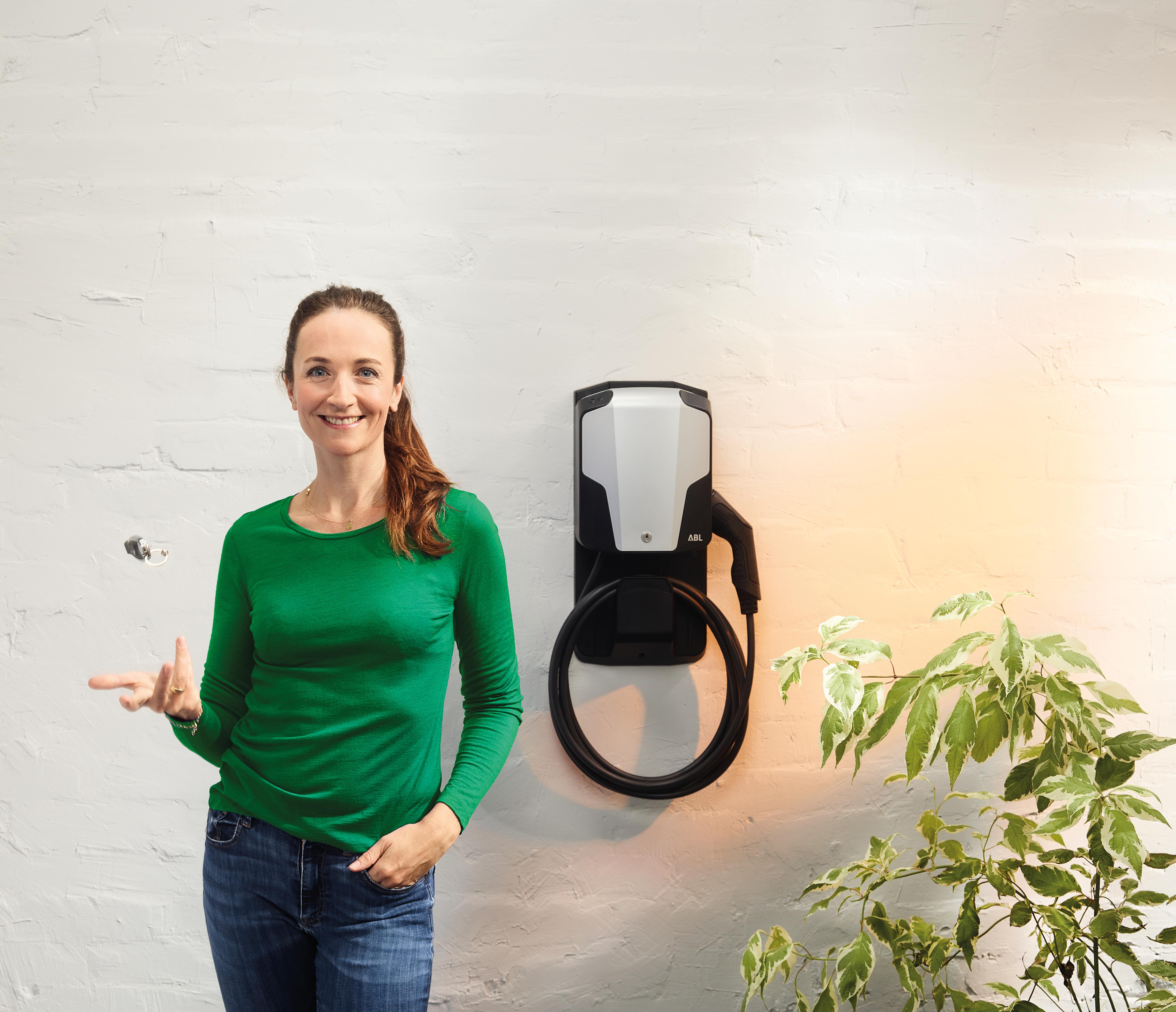 Eine Frau mit grünem Pullover wirft einen Schlüssel hoch. Im Hintergrund hängt an der Wand eine Ladestation für Elektroautos